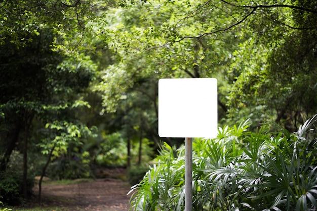 Quadro de avisos vazio branco no parque com fundo da natureza. Foto gratuita