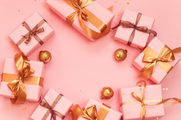 Quadro de banner de natal ou ano novo com bolas douradas, caixas de presente de papel rosa decoradas com fitas de ouro brilhantes em um rosa. Foto Premium