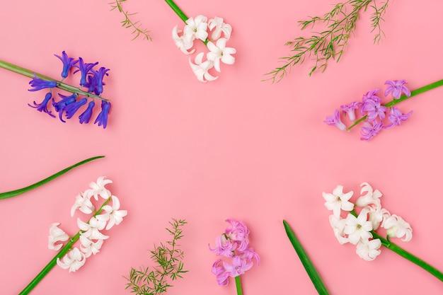Quadro de buquê de flores da primavera de jacintos brancos e lilás sobre fundo rosa vista superior plana leigos Foto Premium