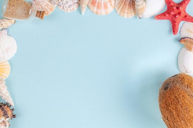 Quadro de conchas, garrafa com areia e coco em um fundo azul Foto Premium