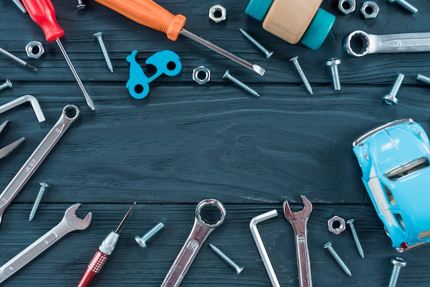 Quadro de diferentes ferramentas e carro de brinquedo na mesa Foto gratuita
