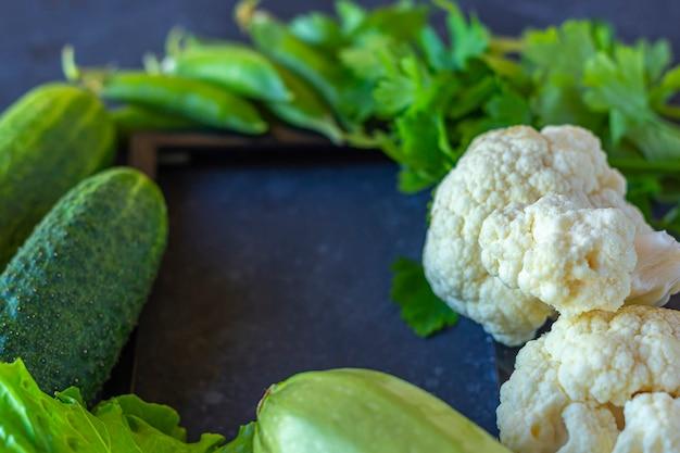 Quadro de diferentes vegetais verdes saudáveis na mesa escura. o conceito de nutrição adequada e alimentação saudável. comida orgânica e vegetariana. vista superior, plana leigos, copie o espaço para texto. Foto Premium