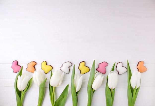 Quadro de doces para celebrar a páscoa. coelho colorido do chocolate e tulipas brancas. Foto Premium