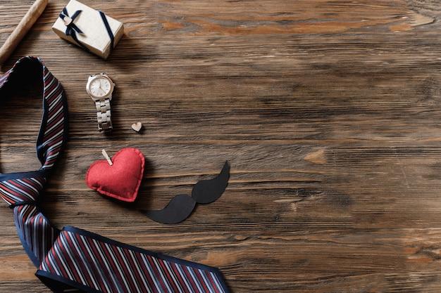 Quadro de férias de caixas de presente, bigode, chapéu de papel, tubo de tabaco, gravata e relógio na mesa de madeira velha. Foto Premium