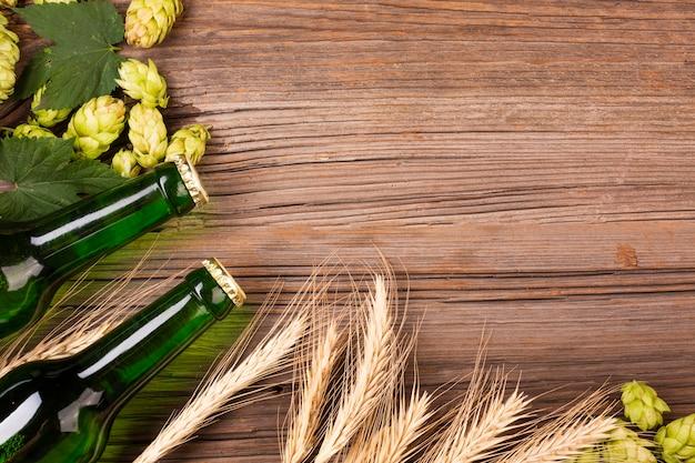 Quadro de garrafas de cerveja e trigo com espaço de cópia Foto gratuita