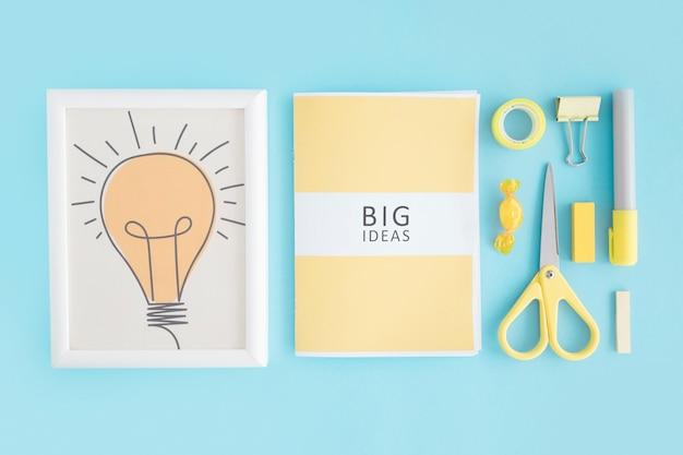 Quadro de lâmpada; livro de grandes idéias e artigos de papelaria em fundo azul Foto gratuita
