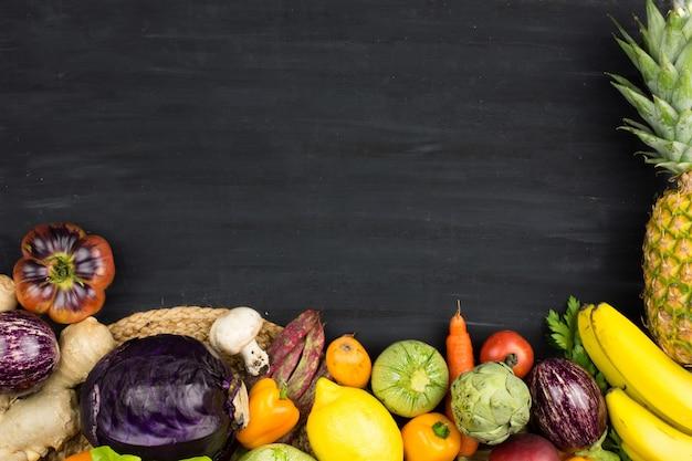 Quadro de legumes frescos e de fruto no fundo de giz preto. Foto Premium