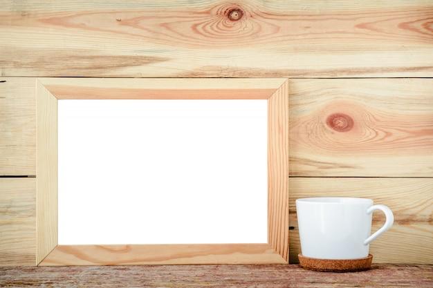 Quadro de madeira isolado com decorações de um copo branco em um fundo de madeira. Foto Premium