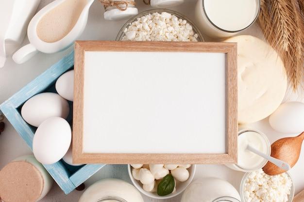Quadro de mock-up cercado por produtos lácteos Foto gratuita