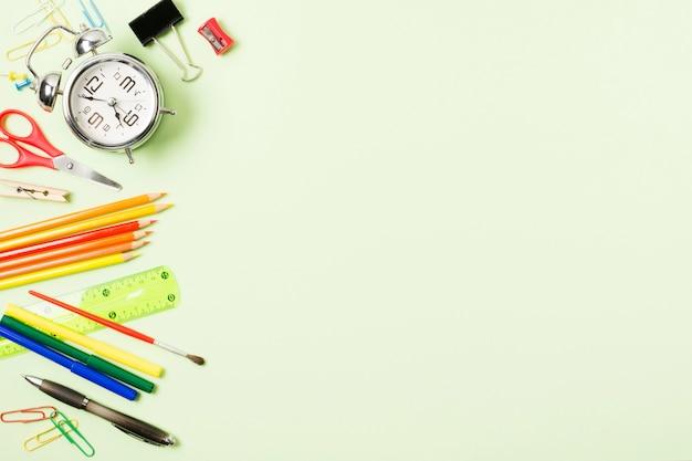 Quadro de suprimentos escolares sobre fundo verde claro Foto gratuita