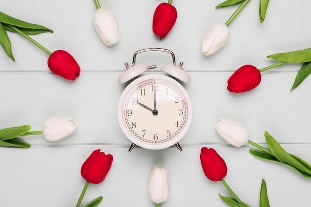 Quadro de tulipas coloridas com relógio na mesa Foto gratuita