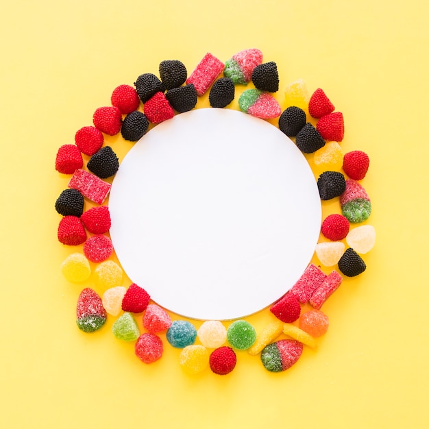 Quadro em branco branco rodeado com doces de gelatina colorida em fundo amarelo Foto gratuita