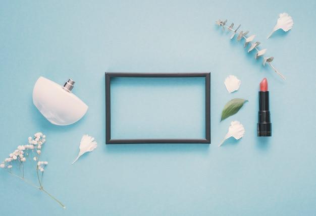 Quadro em branco com batom e plantas na mesa Foto gratuita