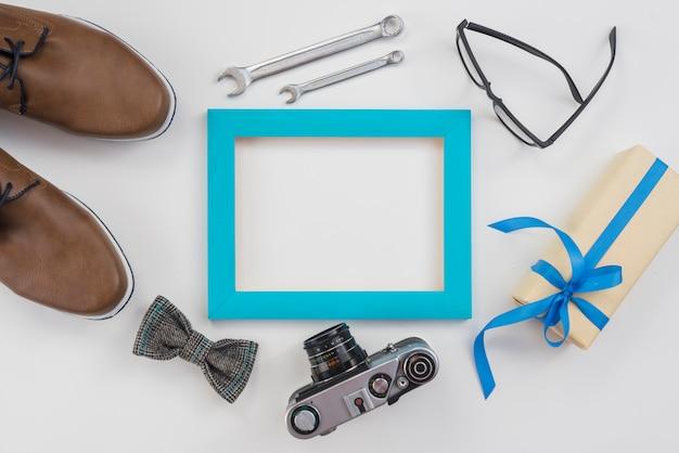 Quadro em branco com câmera, sapatos de homem e presente Foto gratuita