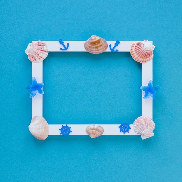 Quadro em branco com conchas do mar na mesa Foto gratuita