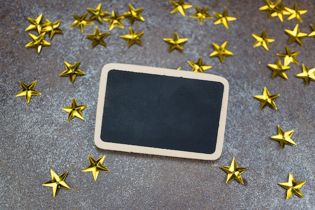 Quadro em branco com estrelas douradas sobre fundo de azulejo rústico Foto Premium