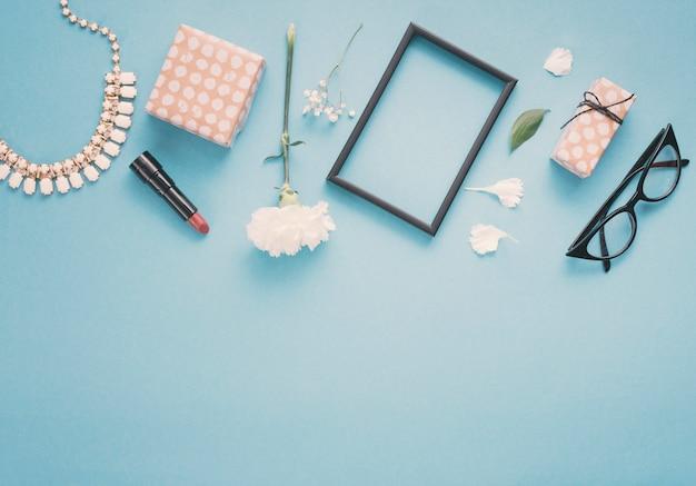Quadro em branco com flores, caixas de presente e batom na mesa Foto gratuita