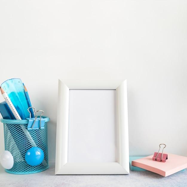 Quadro em branco e ferramentas de escritório na mesa Foto gratuita