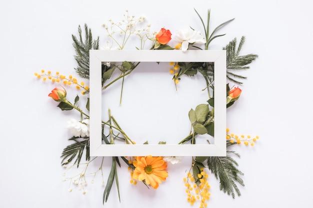 Quadro em branco em diferentes flores na mesa Foto gratuita