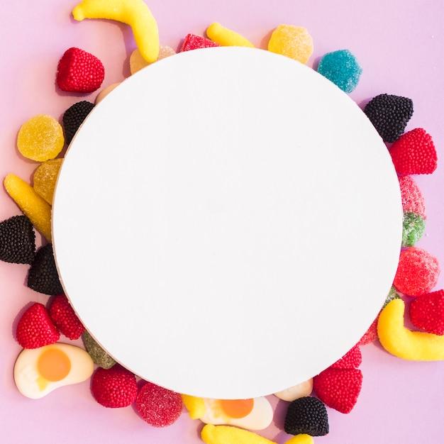 Quadro em branco redondo sobre os doces coloridos em pano de fundo-de-rosa Foto gratuita