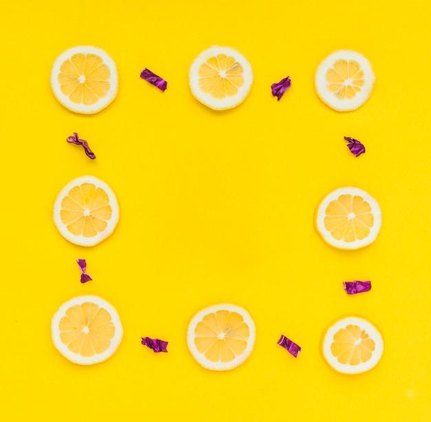 Quadro feito com limões em fatias e repolho roxo picado no fundo amarelo Foto gratuita