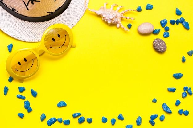 Quadro feito dos óculos de sol com um sorriso, um chapéu, umas pedras decorativas e um shell em um fundo amarelo. vista do topo Foto Premium