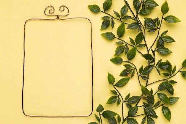 Quadro metálico vazio perto das folhas artificiais na parede amarela Foto gratuita