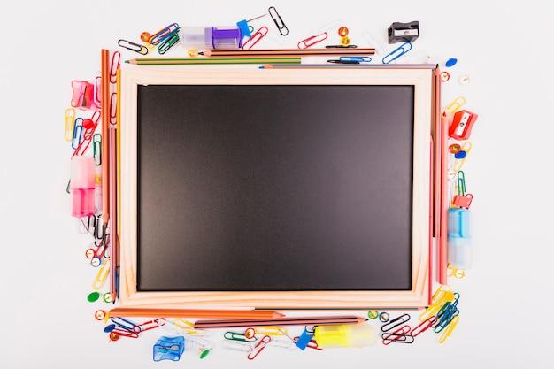 Quadro-negro com papelaria da escola diferente Foto gratuita