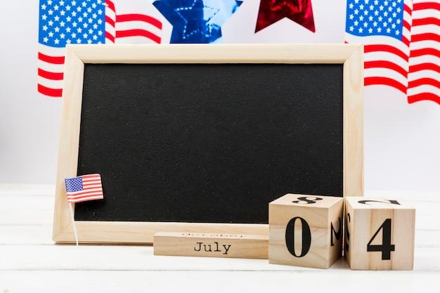 Quadro-negro decorado com pequena bandeira do eua no dia da independência Foto gratuita