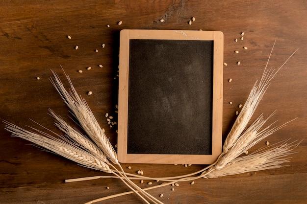 Quadro-negro e spike trigo na mesa de madeira marrom Foto gratuita