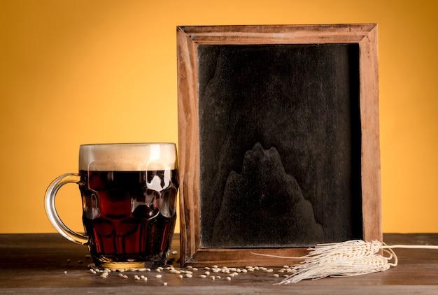 Quadro-negro em pé ao lado do copo de cerveja na mesa de madeira Foto gratuita