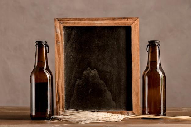 Quadro-negro entre duas garrafas de cerveja na mesa de madeira Foto gratuita