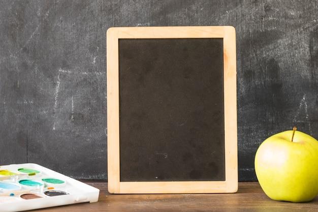 Quadro-negro na mesa com tintas e maçã Foto gratuita