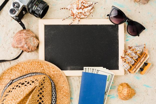 Quadro-negro perto de chapéu com barco de brinquedo e dinheiro entre conchas e câmera Foto gratuita