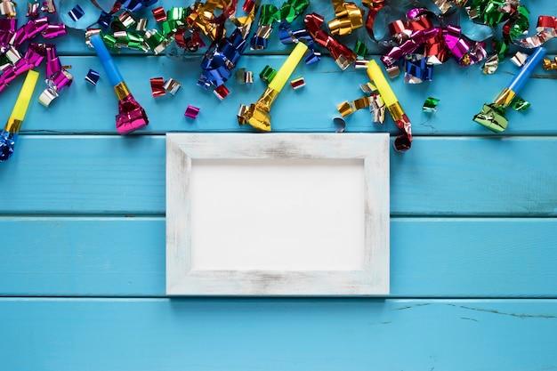 Quadro perto de confetes e chifres de festas Foto gratuita