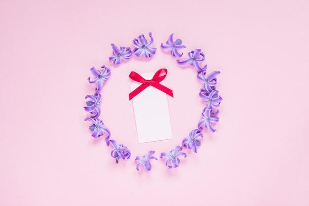 Quadro redondo de jacintos roxos pastel e cartão vazio com laço vermelho em fundo gradiente rosa Foto Premium
