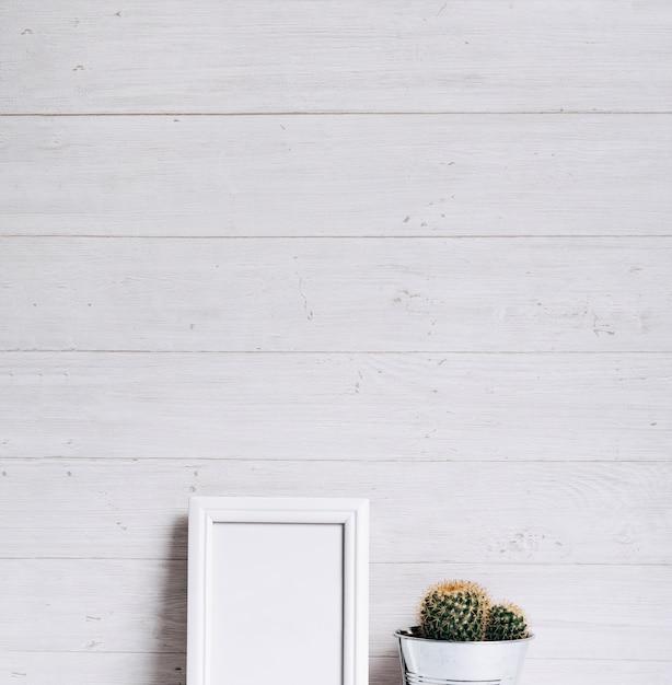 Quadro vazio branco e cactos contra fundo de madeira Foto gratuita