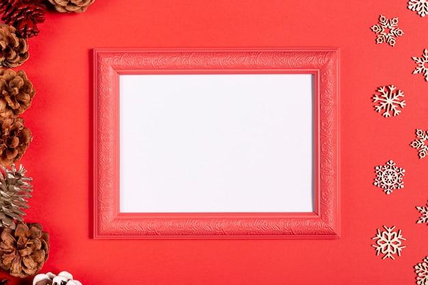 Quadro vintage e flocos de neve na mesa vermelha Foto gratuita