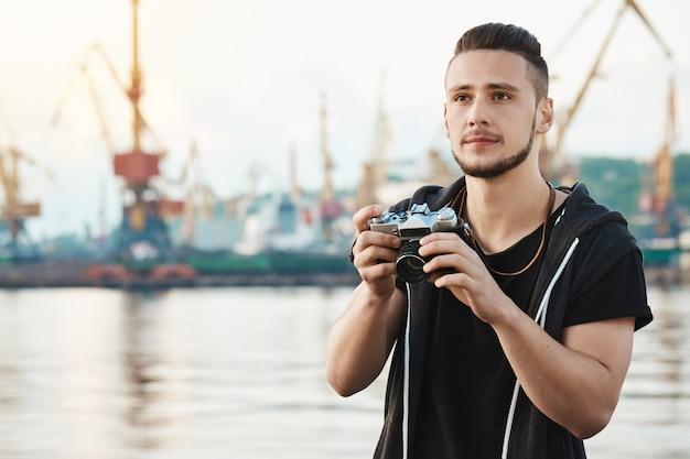 Quando o hobby se torna um trabalho amado. retrato de sonhador jovem criativo com barba segurando a câmera e olhando de lado com expressão satisfeita pensativa, tirando fotos do porto e do mar enquanto caminhava Foto gratuita