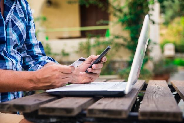 Quarenta anos de homem caucasiano olhando o cartão de crédito enquanto trabalhava no computador portátil no terraço do jardim durante o dia de verão ensolarado. estilo de vida moderno - fim de semana rural e conceito de compras on-line. Foto gratuita