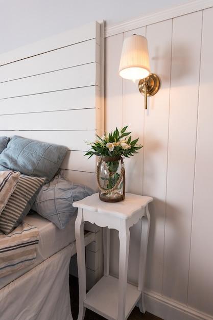 Quarto bem iluminado e confortável com design de interiores. estilo escandinavo. flores na mesa de cabeceira. travesseiro na cama. interior do quarto. uma pequena lâmpada acesa acima de uma mesa. Foto Premium