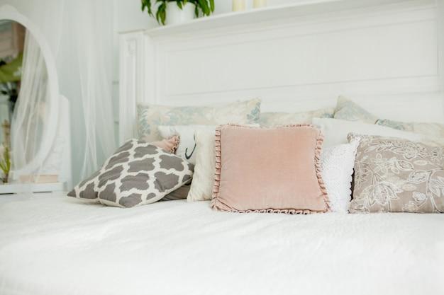 Quarto branco estilo escandinavo. quatro travesseiros estão na cama. interior moderno Foto Premium