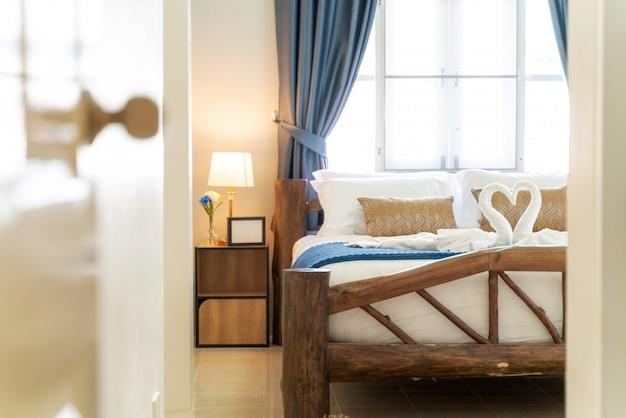 Quarto brilhante da casa com toalha de cisne na cama Foto Premium