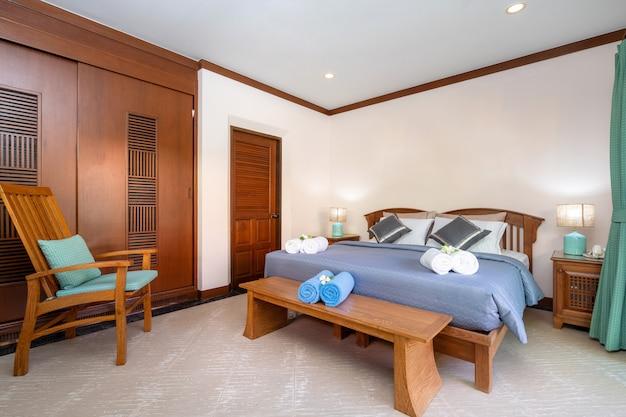 Quarto espaçoso com lençol azul e lençol de madeira Foto Premium