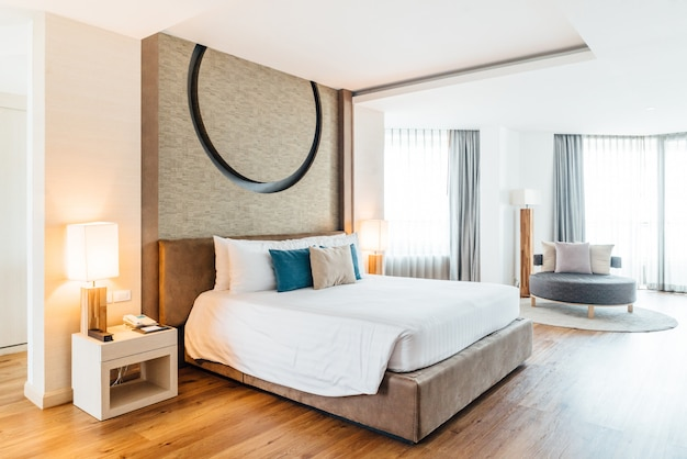 Quarto principal decorado com tons claros e quentes, cobertor branco, travesseiros azuis e cinzas. Foto Premium