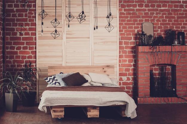 Quarto simples com cama de casal, parede de tijolo vermelho e grande janela Foto Premium