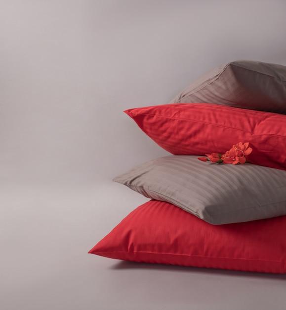 Quatro coxins empilhados com a flor vermelha contra o fundo branco. Foto Premium