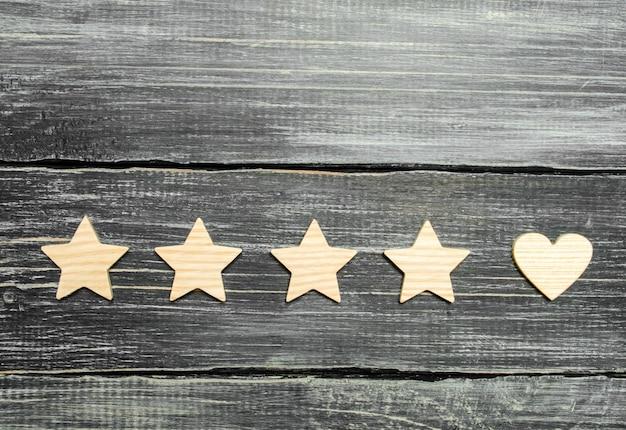 Quatro estrelas e um coração em um fundo escuro. seleção dos clientes usuários. Foto Premium