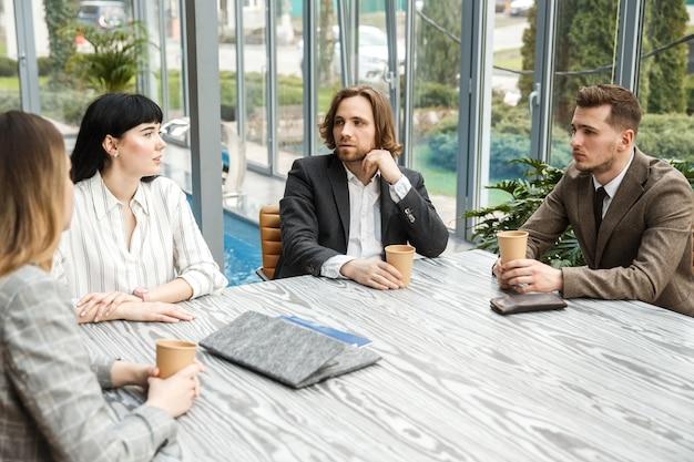 Quatro funcionários de escritório estão sentados em uma reunião Foto Premium