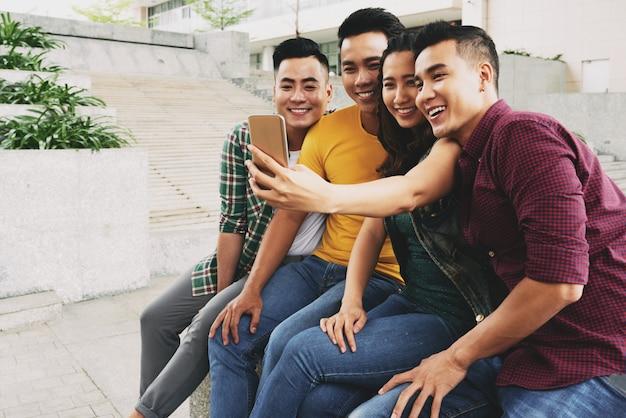 Quatro jovens asiáticos vestidos casualmente sentados juntos na rua e tomando selfie Foto gratuita